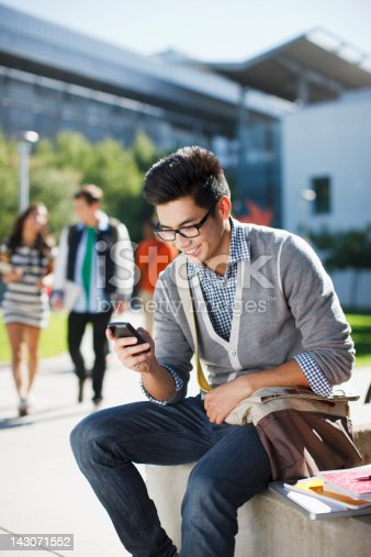 istock Smiling student using cell phone outdoors 143071552