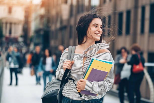 Estudante, caminhando para o vento a sorrir - foto de acervo