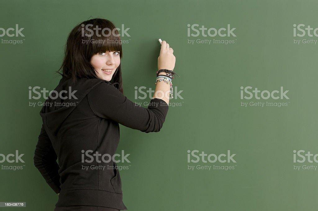 smiling student writing on blackboard royalty-free stock photo