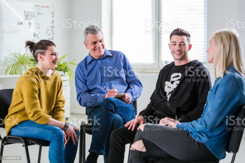 Smiling students and therapist looking at woman Smiling students and therapist looking at young woman in lecture hall. Male and female are sitting at university. They are in group therapy session. 18-19 Years Stock Photo