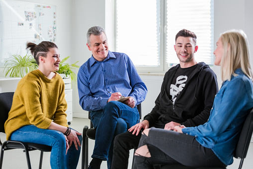 Smiling Students And Therapist Looking At Woman Stock Photo - Download Image Now