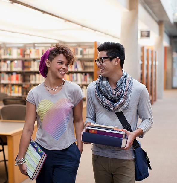 ritratto di un sorridente studenti parlando in libreria - two students together asian foto e immagini stock