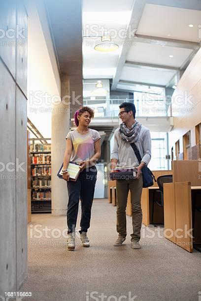 Smiling students talking in library picture id168116653?b=1&k=6&m=168116653&s=612x612&h=gwln9dk1sx1vmaxblezgyqz8ps09ljivsns0e5rgazw=