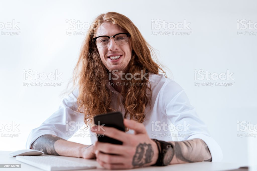 smiling stylish tattooed businessman with curly hair holding smartphone royalty-free stock photo