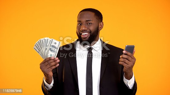 istock Smiling Successful black male in suit holding phone and dollar bills, cashback 1152597946