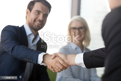 istock Smiling successful businessmen in suits shaking hands expressing respect 1128967612