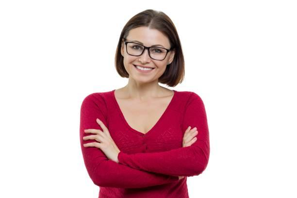 Sonriente a mujer de mediana edad confía en éxito en vasos con los brazos cruzados mirando a cámara sobre fondo blanco, aislado - foto de stock