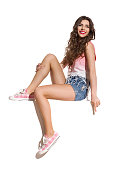Beautiful young woman in pink top, jeans shorts and pink sneakers sitting on the top of white banner, looking at camera and pointing down. Full length studio shot isolated on white.