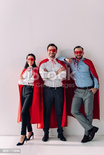 516318379istockphoto smiling super businesspeople in masks and capes looking at camera on white 955172856