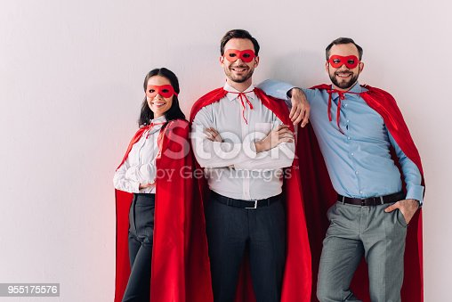516318379istockphoto smiling super businesspeople in masks and capes looking at camera isolated on white 955175576