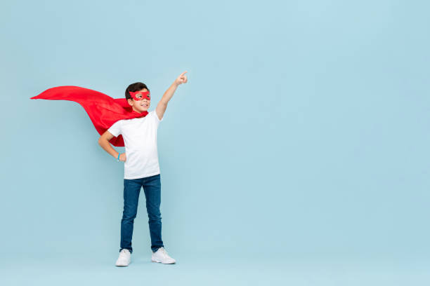 Smiling superhero boy in red mask and cape pointing hand aside stock photo