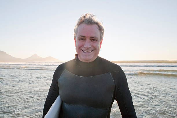 Smiling surfer in water  wetsuit stock pictures, royalty-free photos & images