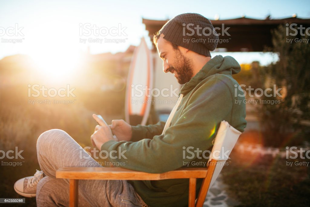 Smiling surfer using smartphone stock photo