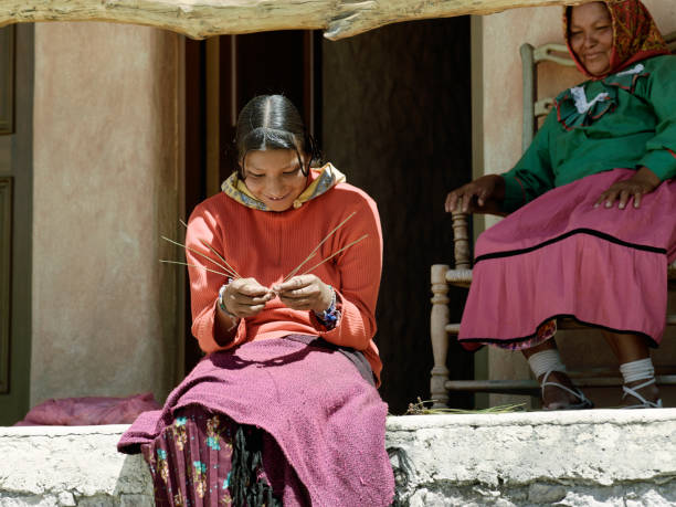 smiling tarahumara woman sitting outdoors and making pine-needle baskets - native american reservation stock photos and pictures