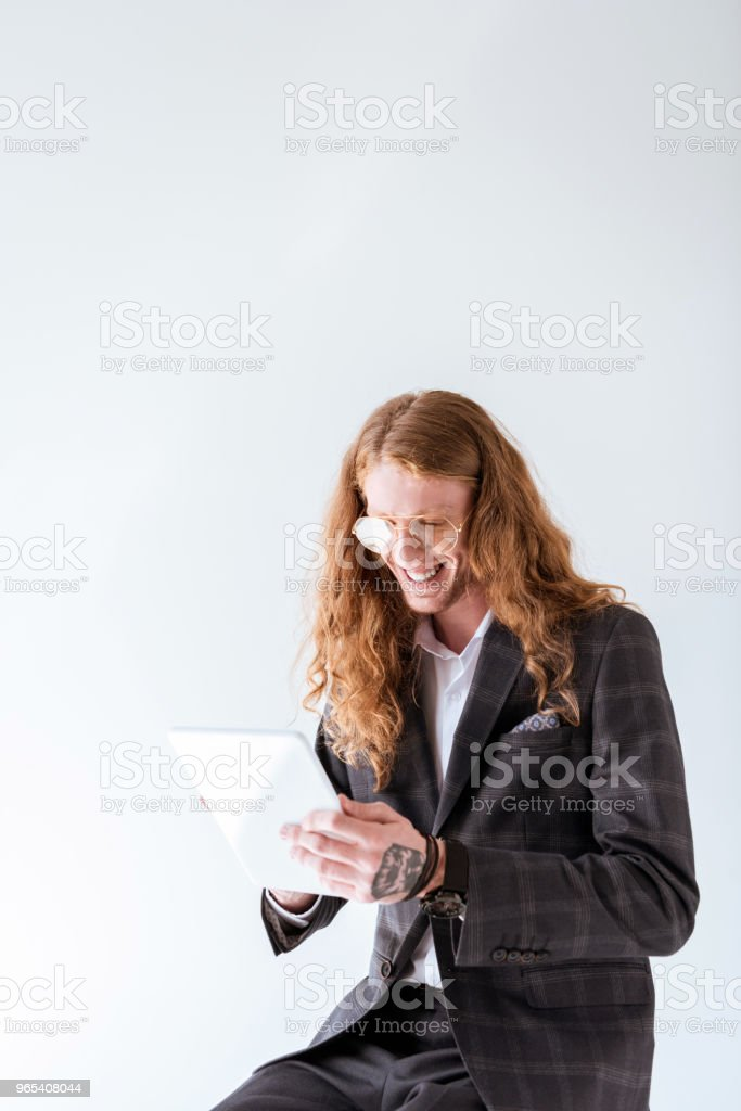 smiling tattooed businessman with curly hair using tablet isolated on white zbiór zdjęć royalty-free
