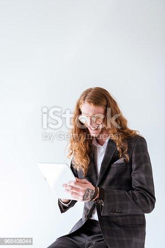 Smiling Tattooed Businessman With Curly Hair Using Tablet Isolated On White - Stockowe zdjęcia i więcej obrazów Białe tło