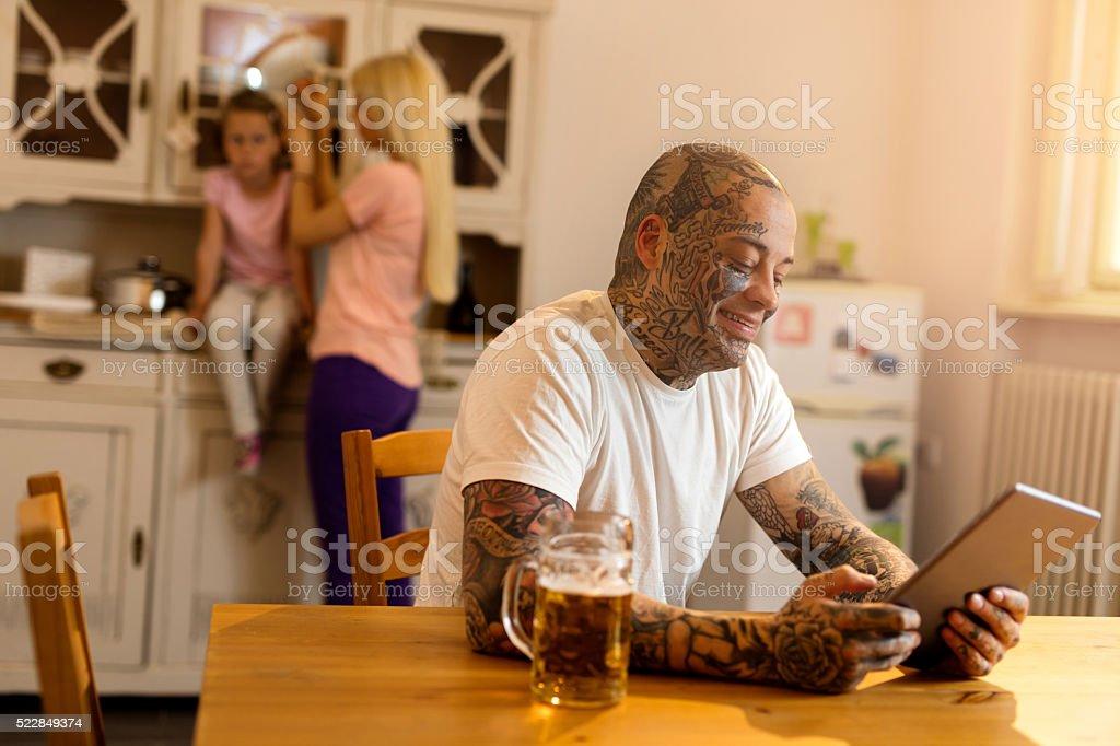 Lächelnd tätowiert Mann mit Touchpad in der Küche. – Foto