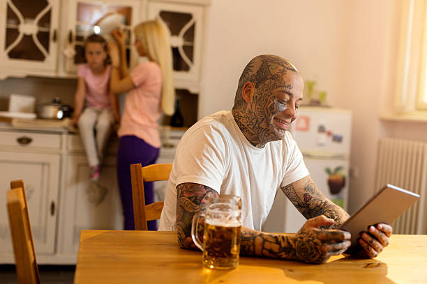 Smiling tattooed man using touchpad in the kitchen. stock photo