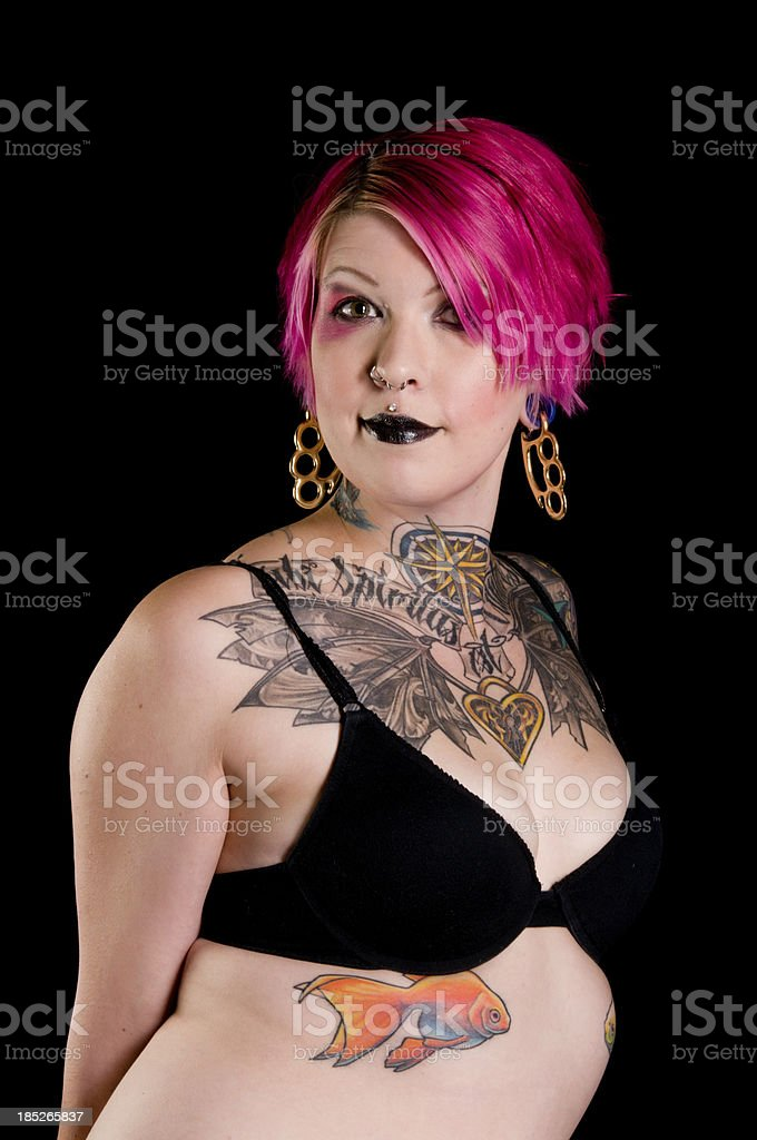 Smiling tattooed woman with pink hair. stock photo