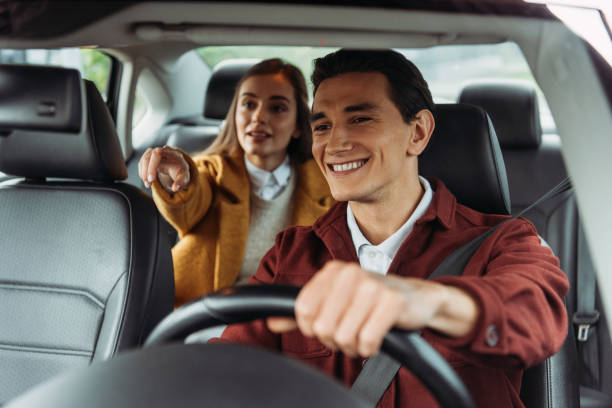 Smiling taxi driver with woman passenger pointing on road stock photo