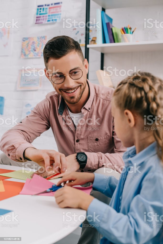 smiling teacher and cute preschooler cutting papers with scissors att able in classroom stock photo