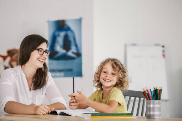 Smiling teacher and happy kid doing homework after classes stock photo