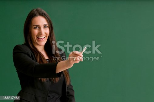 istock smiling teacher at blackboard 185217484