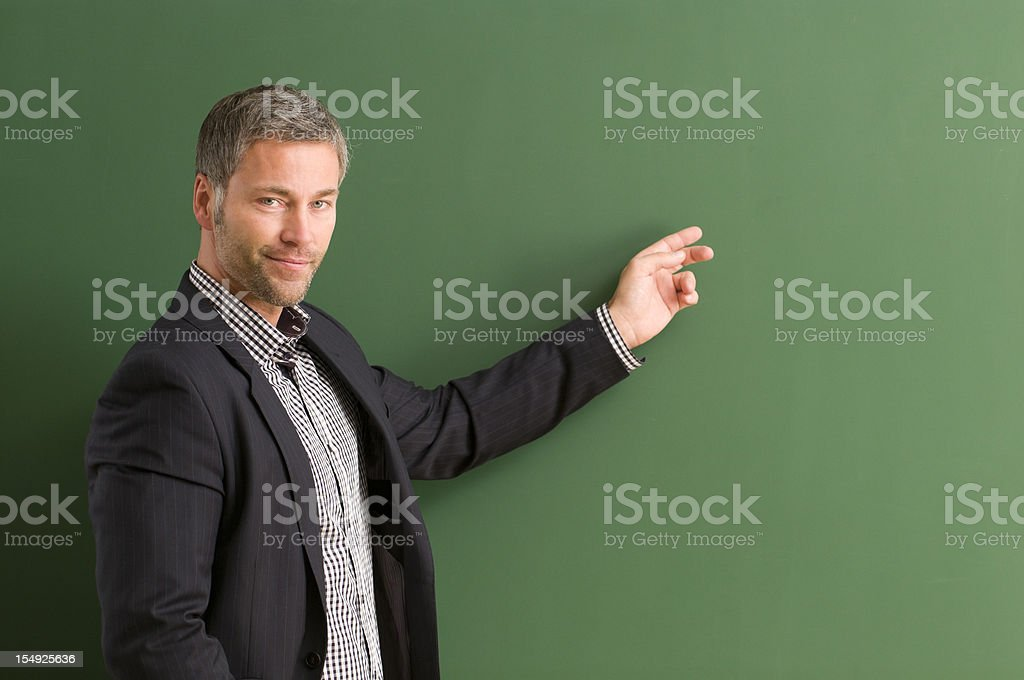 smiling teacher directing at blackboard stock photo