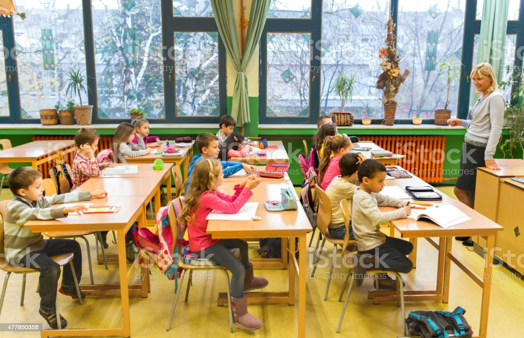 Smiling teacher having a class with group of elementary students. stock photo