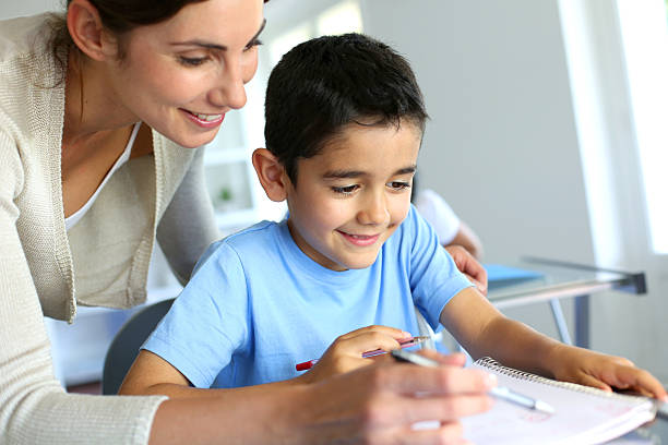 Smiling teacher helping kid stock photo