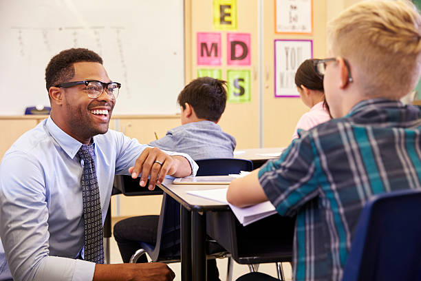 Smiling teacher kneeling beside elementary school pupil's desk stock photo