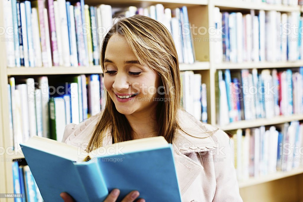 Smiling teacher, librarian, or mother reading in the library stock photo