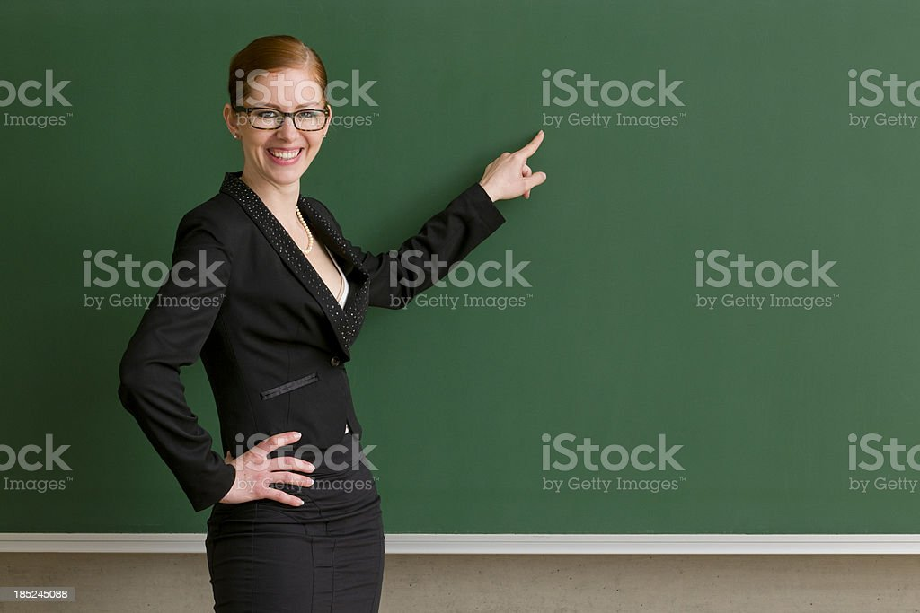 smiling teacher pointing at blackboard royalty-free stock photo