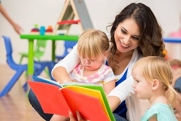 smiling teacher reading a colorful book to cute preschool girls - erzieherin stock-fotos und bilder