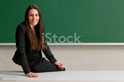 istock smiling teacher sitting on desk 185220246