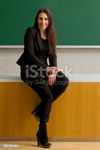 istock smiling teacher sitting on desk 185280464