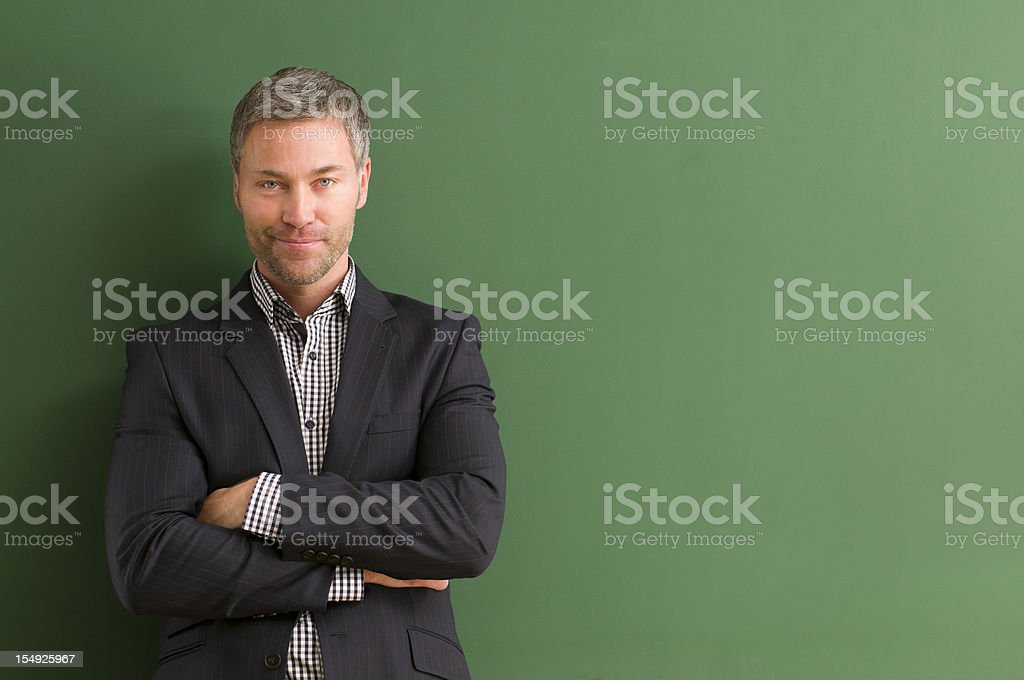 smiling teacher with arms crossed at blackboard stock photo