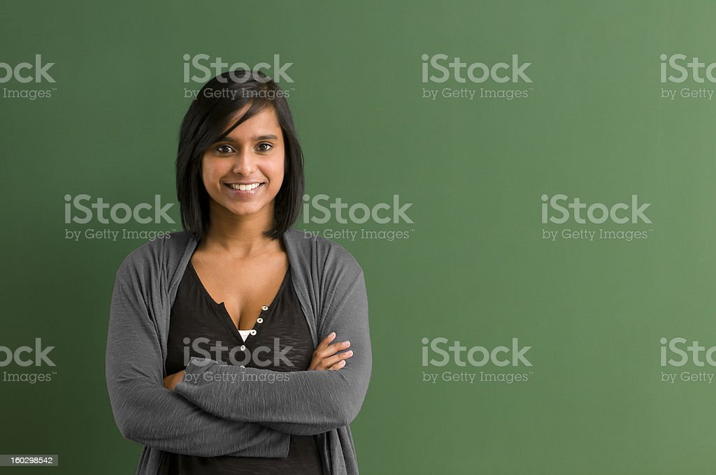 Smiling teacher with arms folded in front of blackboard圖像檔