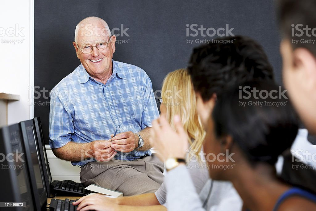 Smiling teacher with students in computer lab royalty-free stock photo