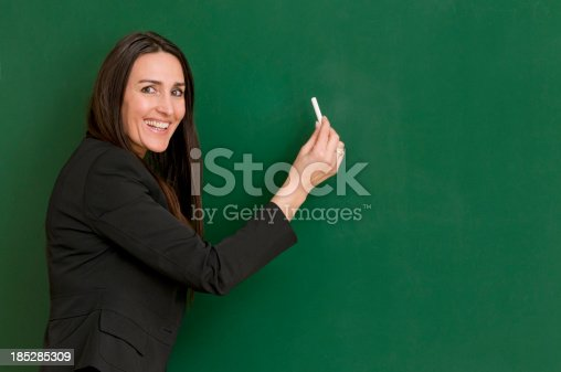 istock smiling teacher writing at blackboard 185285309