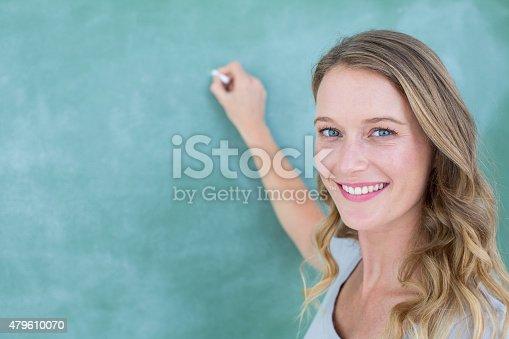 istock Smiling teacher writing on blackboard 479610070