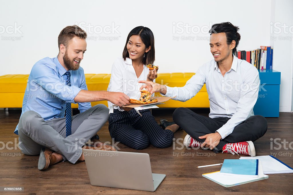 Smiling team having informal meeting with pizza - Photo