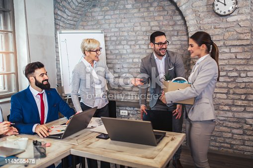 924520144 istock photo Smiling team leader executive introducing new just hired female employee to colleagues. 1143668478