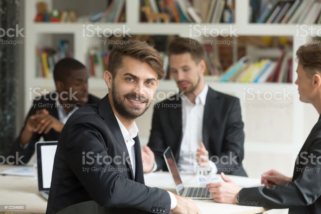 Smiling team leader looking at camera on group corporate meeting stock photo