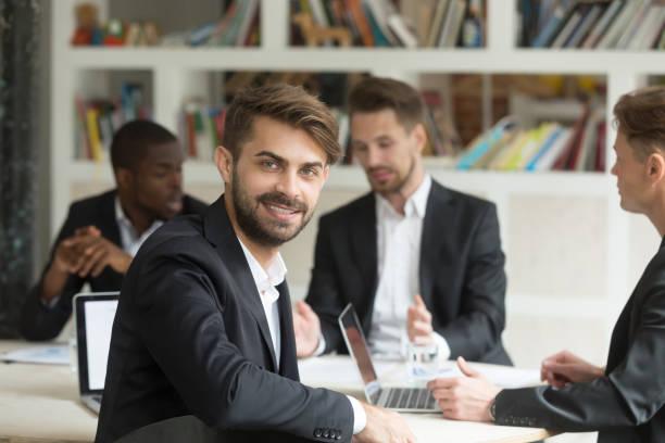 lächelnden blick in die kamera auf gruppe firmenmeeting teamleiter - projektmanager stock-fotos und bilder