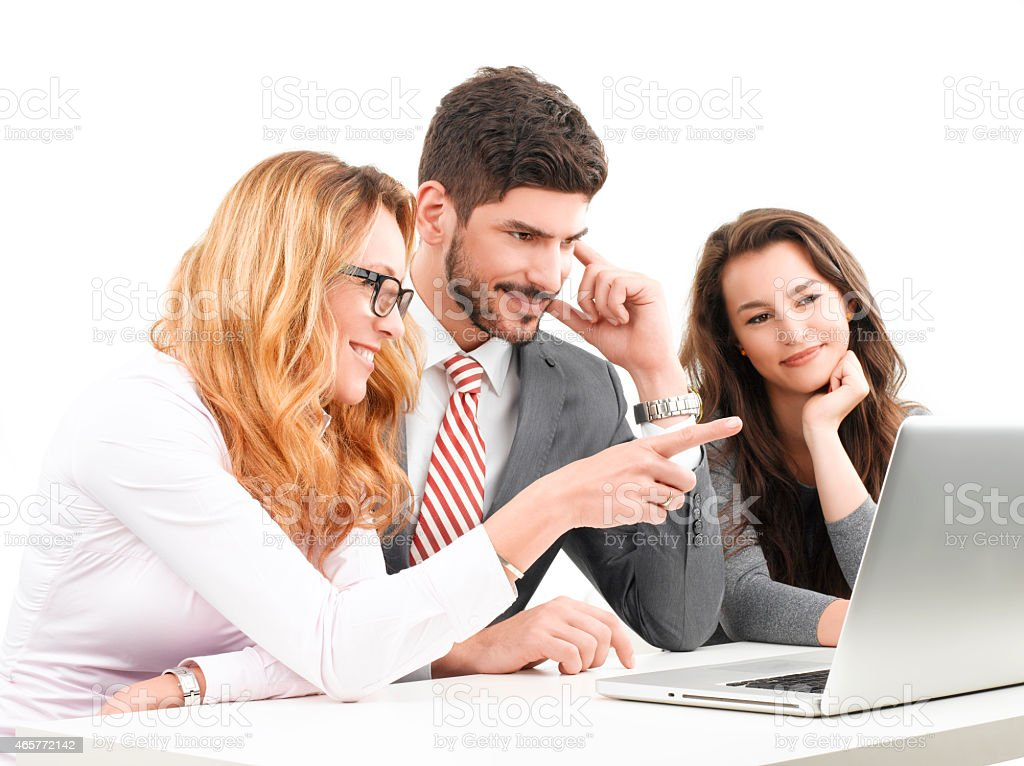 Smiling team of colleagues sitting at a laptop together stock photo