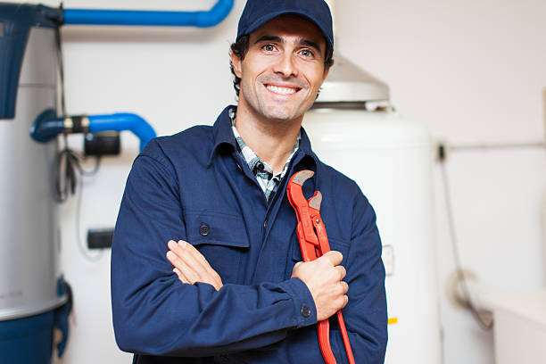 Smiling technician repairing an hot-water heater Smiling technician repairing an hot-water heater pipefitter stock pictures, royalty-free photos & images