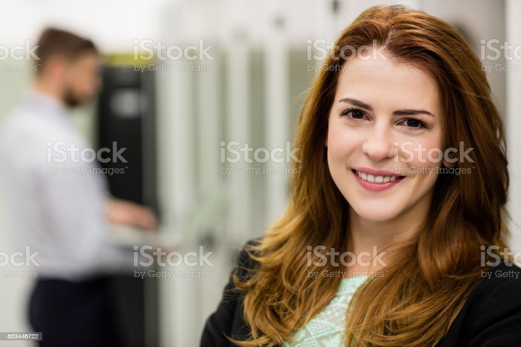 Smiling technician standing in a server room stock photo