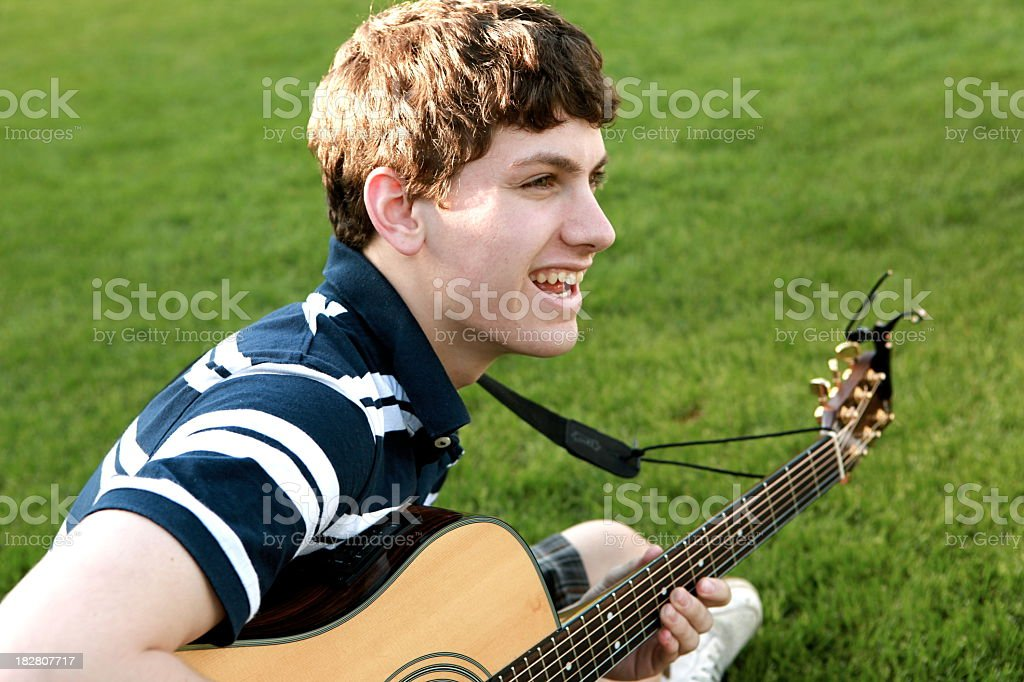 Smiling teen boy playing guitar outdoors on the grass royalty-free stock photo