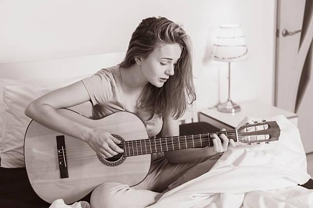 smiling teen girl playing  on guitar - kreatives schreiben übungen stock-fotos und bilder